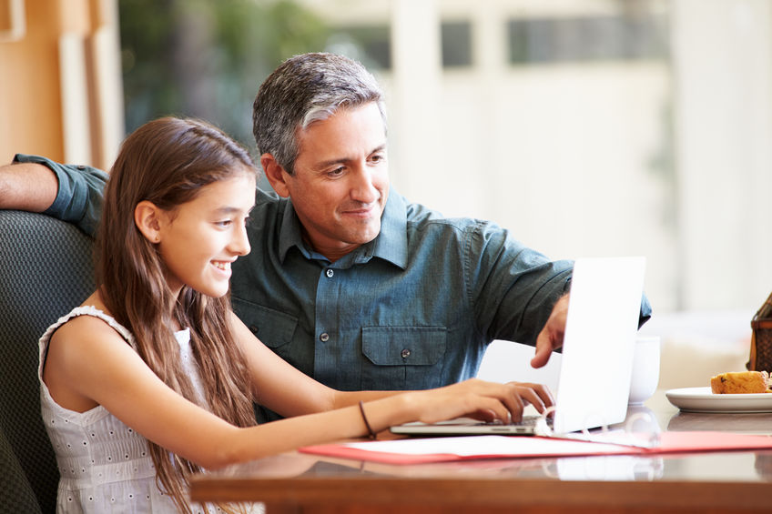 31067204 - father and teenage daughter looking at laptop together